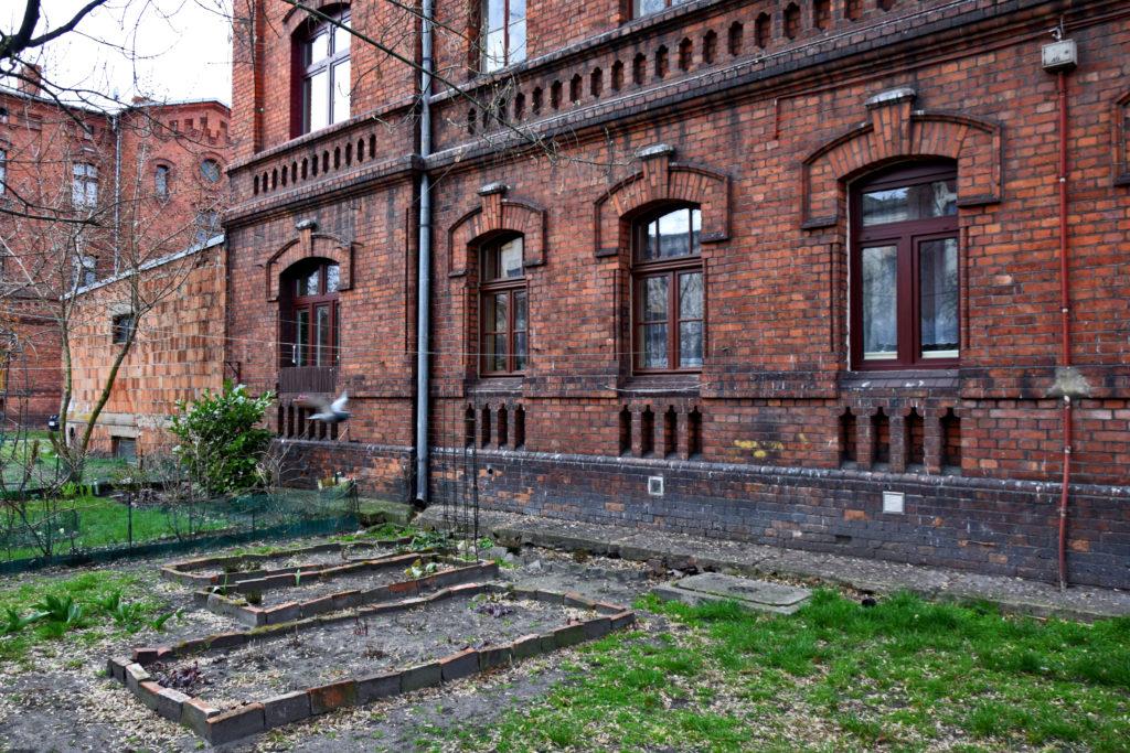 Żyrardów, ceglana zabudowa. Niektórzy mają przed domem niewielkie ogródki - drobna rekompensata ciasnych mieszkań.