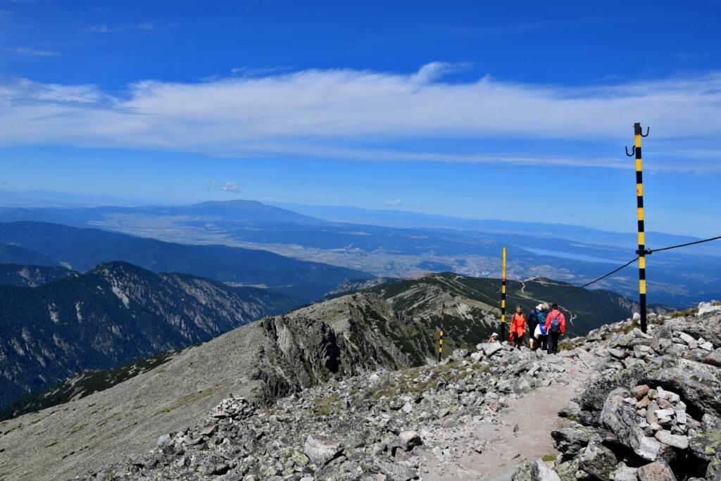 Musała, schodzimy ze szczytu. Wysokie słupki wytyczają szlak zimowy, gdy na szlaku zalegają metry śniegu.